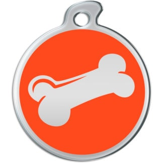 Picture of round dog tag decorated with metallic bone on red background.