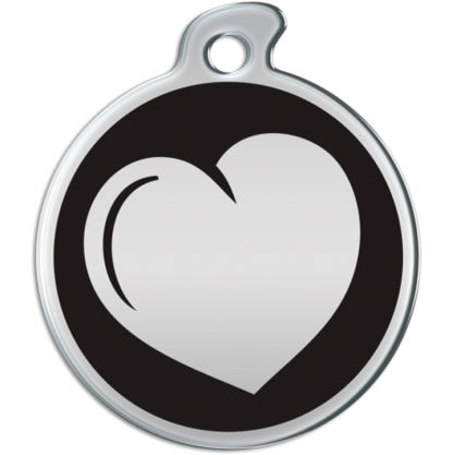 Image of a round dog tag with a  metallic heart on a black background.